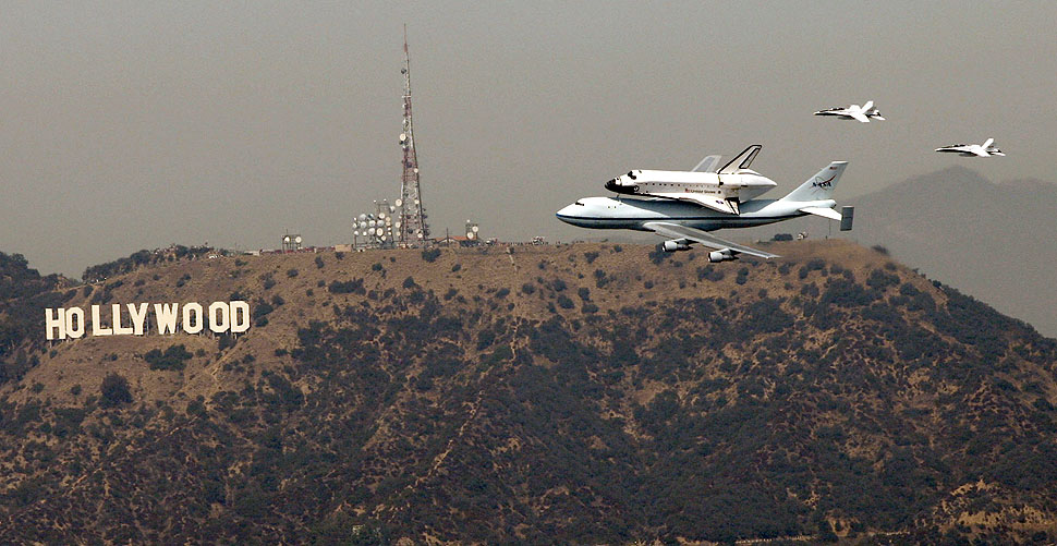 Seen from the US Bank Tower in downtown Los Angeles, the space shuttle Endeavor passes the Hollywood sign as the retired space shuttle makes the rounds of the Los Angeles and Orange County areas before landing at LAX.